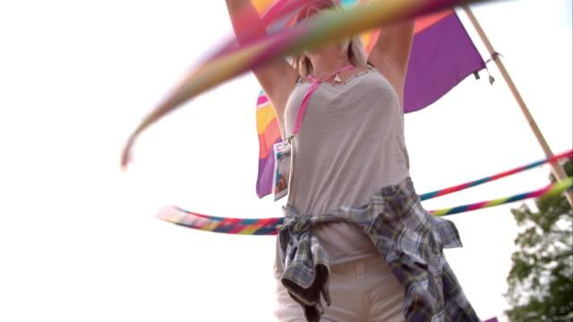 ragazza danza hula-fa l'hula hoop con due canestri a un festival, rallentatore - pantaloncini video stock e b–roll
