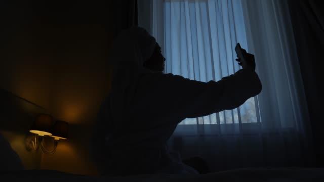 stockvideo's en b-roll-footage met meisje in een badjas zit voor het hotelraam op het bed - photography curtains