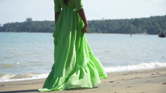 A girl in a beautiful, light, lush green dress is walking along the beach. A girl in a beautiful, light, lush green dress is walking along the beach. Back view. Slow motion. Thailand. military private stock videos & royalty-free footage