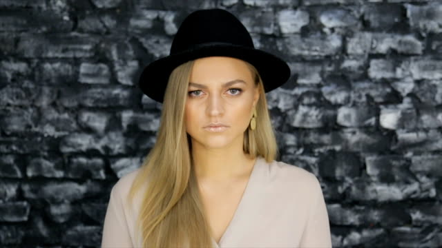 A girl in a black hat and a gray shirt posing against a brick wall background Model in a black hat and gray shirt posing against a textured wall eyeliner stock videos & royalty-free footage