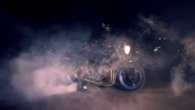 girl in a black leather suit on a streetbike burning rubber. - bike tire tracks video stock e b–roll