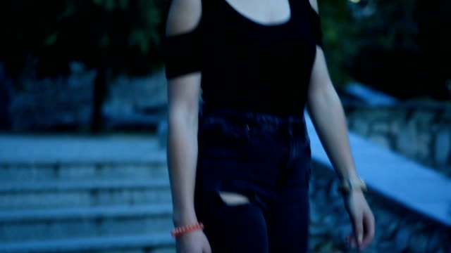 girl in a black t-shirt and jeans descends the stairs on the street