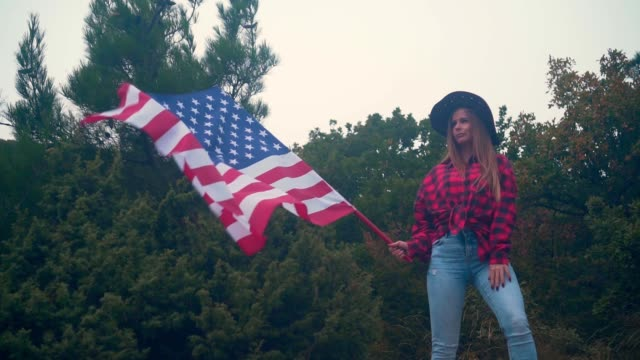 A girl in a cowboy hat, a red stylish shirt and blue jeans holds in her hand a large American flag. Patriotism concept