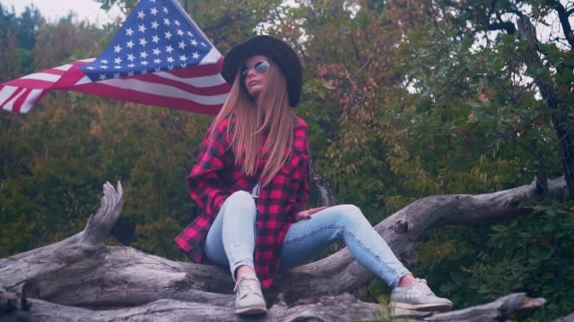 A girl in a cowboy hat sits on a log, and in the background an American flag flutters in the wind. American patriot