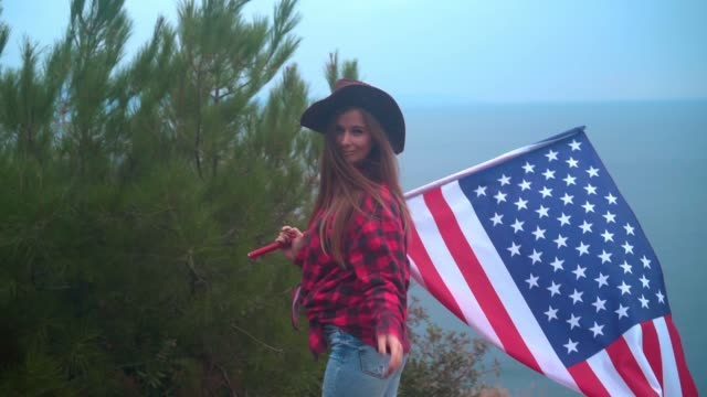 Girl in a cowboy hat with an American flag on a background of the sea. The concept of patriotism. USA National Day