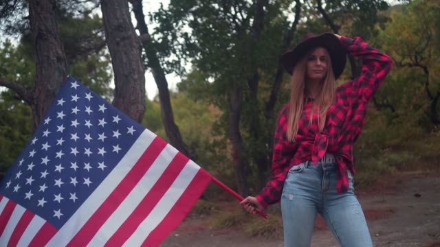 Girl in a cowboy hat with an American flag. The concept of patriotism. USA National Day