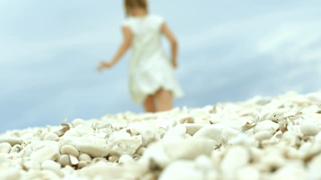 Girl in a dress collecting white pebbles by the seashore video