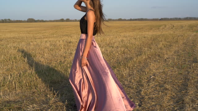 vídeos de stock e filmes b-roll de girl in a dress in a field. long skirt swaying in the wind - saia
