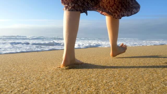mädchen in einem kleid geht entlang des ozeans barfuß auf dem sand nahaufnahme, eine welle wäscht ihre füße mit spritzern zeitlupe - niedrig stock-videos und b-roll-filmmaterial