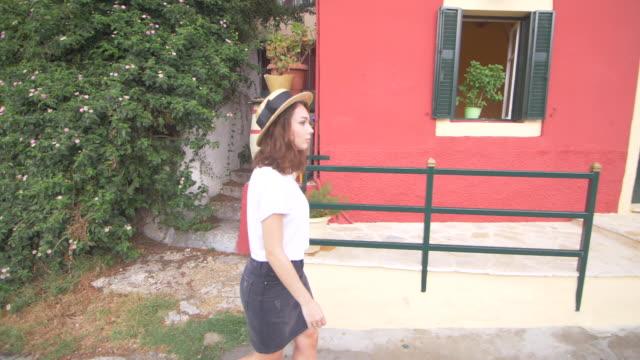 a girl in a dress walks at the street. walk in the blooming street. a beautiful girl is walking in the street. lifestyle. - wschodnio europejski filmów i materiałów b-roll