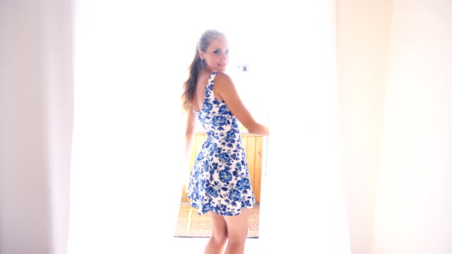 girl in a dress with flowers stands at the window posing smiling video