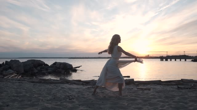 vídeos de stock e filmes b-roll de girl in a flowing dress dancing by the sea at sunset. - tule têxtil