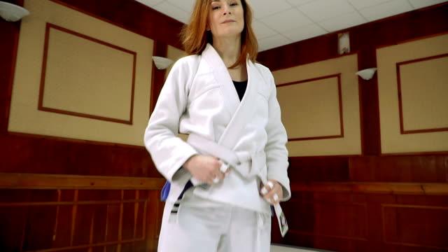 eine mädchen in einem kimono knetet vor dem training im judo und jiu-jitsu - karate stock-videos und b-roll-filmmaterial