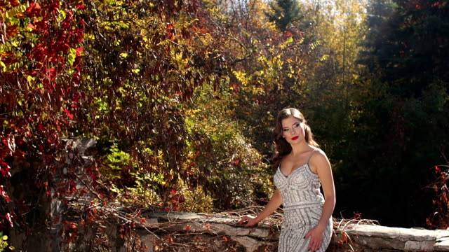 Girl in a long silver evening dress walks in an old abandoned park in the autumn
