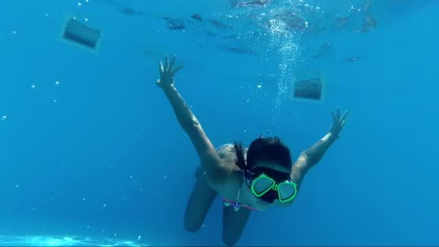 flickan i en mask dyk i poolen ser in i kameran, bubblor - endast flickor bildbanksvideor och videomaterial från bakom kulisserna