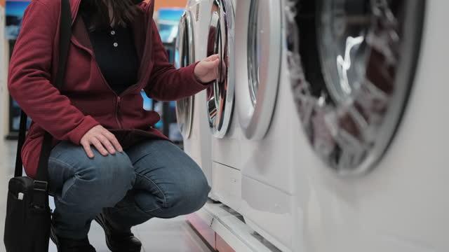 ragazza con una maschera medica compra una lavatrice in un negozio - elettrodomestico attrezzatura domestica video stock e b–roll