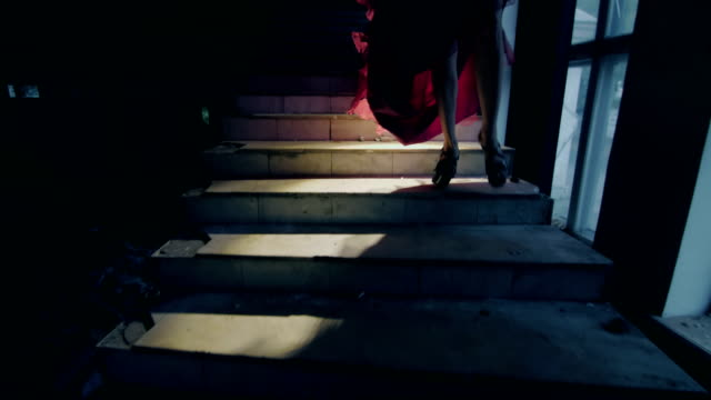 girl in a red dress is going down the stairs video