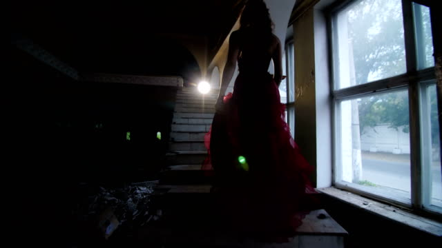 girl in a red dress rises up the stairs video