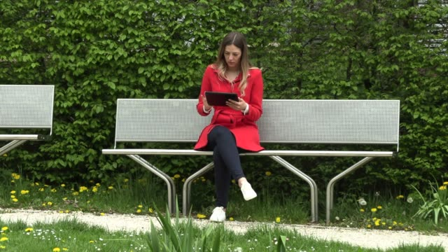 girl in a red dress with a tablet on the street in the park - садовая скамья стоковые видео и кадры b-roll