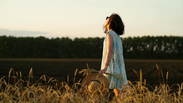 girl in a straw hat and dress walking through a golden wheat field at sunset video
