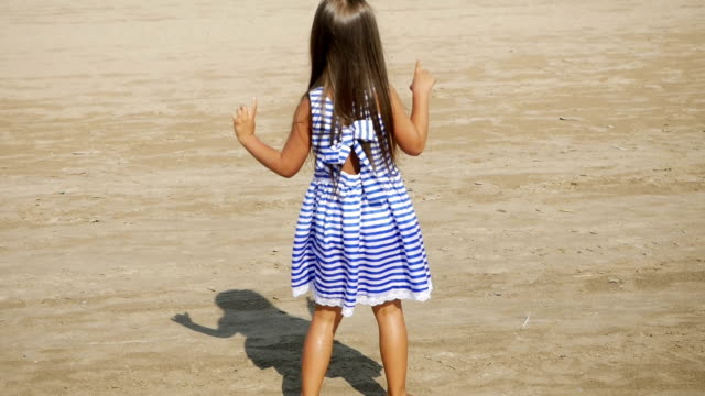 girl in a striped dress and long hair dancing back