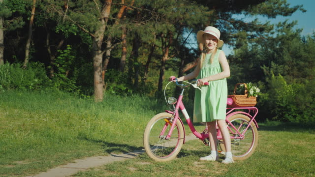 a girl in a summer dress is standing near a bicycle, looking at the camera. with her basket of wildflowers - cestino della bicicletta video stock e b–roll