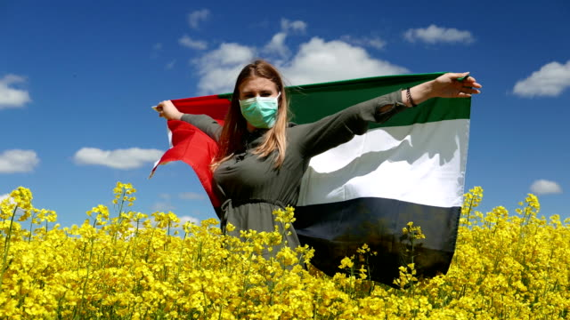 girl in a surgical mask on a beautiful rapeseed field with the flag of arab emirates - uae flag filmów i materiałów b-roll