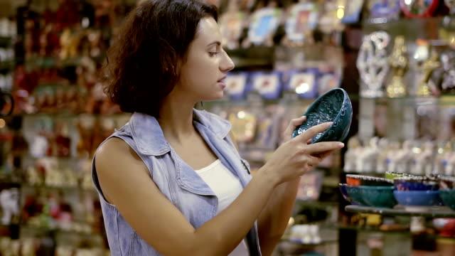 vídeos de stock, filmes e b-roll de uma garota em uma loja de souvenirs oriental. uma bela morena escolhe uma lembrança de uma viagem ao oriente - cerâmica artesanato