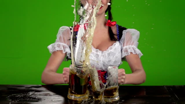 Girl in Bavarian costume breaks glasses with beer. Green screen. Slow motion video