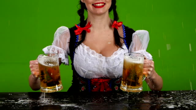 Girl in Bavarian costume pours beer over. Green screen. Slow motion video