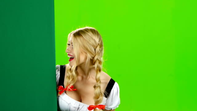 Girl in bavarian costume shows thumb from the board. Oktoberfest. Green screen video