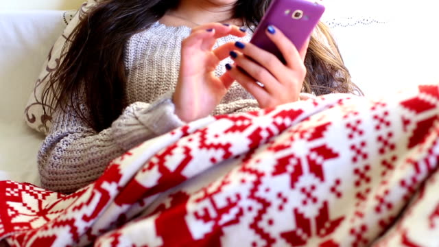 Girl in bed using phone video