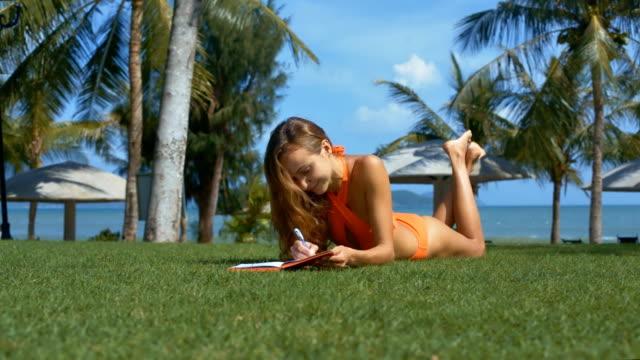 Girl in Bikini Makes Notes in Book on Green Grass