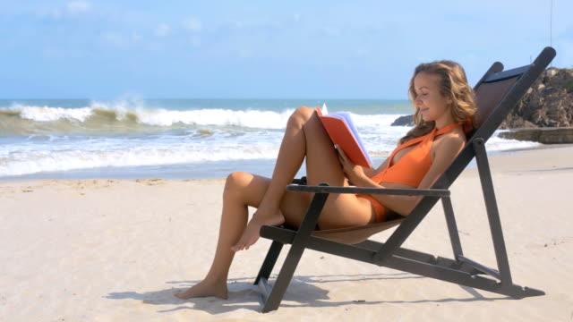 Girl in Bikini Sits and Reads Book against Ocean