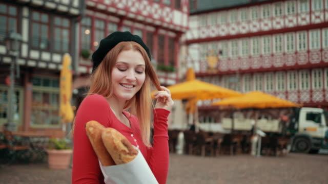 dziewczyna w czarnym berecie trzymając papier owinięte bochenki i pokazuje kciuki w górę. - francuska kuchnia filmów i materiałów b-roll
