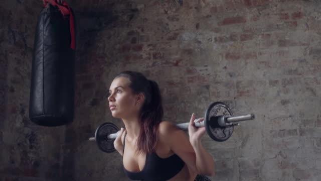 ragazza in abbigliamento sportivo nero che fa squat con bilanciere sullo sfondo di un muro di mattoni - dorso umano video stock e b–roll