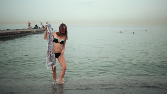 flicka i svart baddräkt, håller pareo, snurrar runt och poserar på stranden - sarong bildbanksvideor och videomaterial från bakom kulisserna