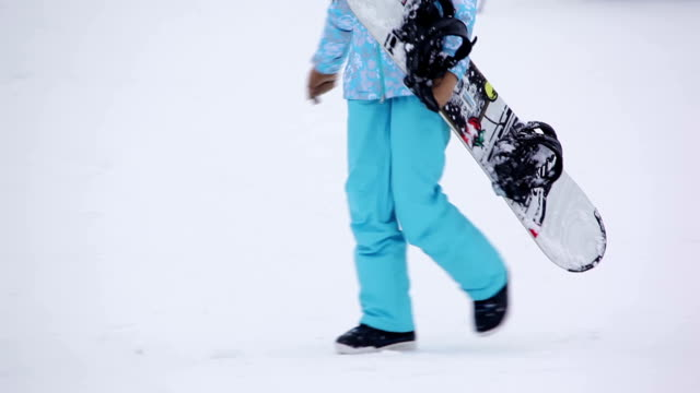 Girl in blue pants with snowboard video