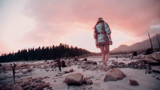 Girl in boho fashion dress in an evening landscape video
