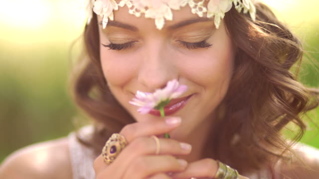 Girl in boho fashion smelling a flower in summer park video