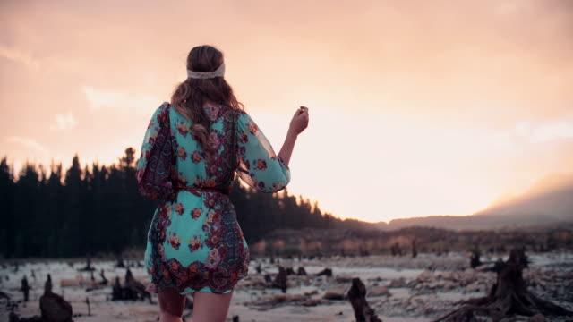 vídeos de stock, filmes e b-roll de garota em estilo boho moda em pé, na água, ao pôr do sol - boho