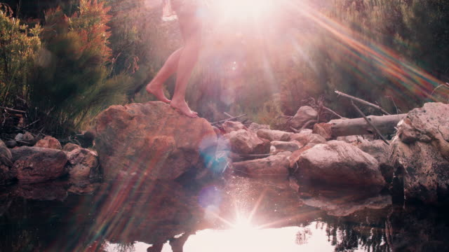Girl in boho floral dress stepping over stones at a lake video