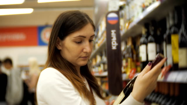A girl in casual clothes chooses wine in a supermarket. Holds a bottle of wine from the shelf in the store. Side view