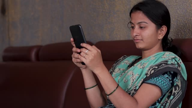 Girl in casual dress busy on mobile while sitting on sofa at home - concept of Indian woman using social media, Internet, digital divide and technology at home.