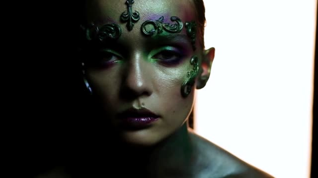 Girl in creative makeup on a black background looks into the camera and moves Girl in creative makeup on a black background looks into the camera and moves sideways glance stock videos & royalty-free footage