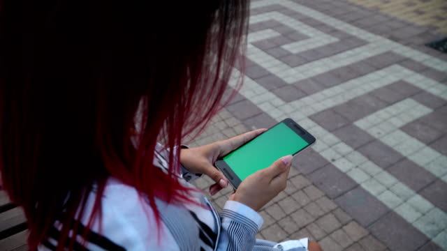Girl in dress seated in park and use smart phone CHROMA KEY screen video
