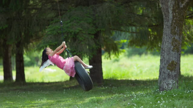 Girl in fairy princess costume on tire swing video