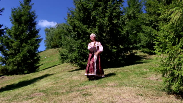 Girl in folk costume dancing on the grass video