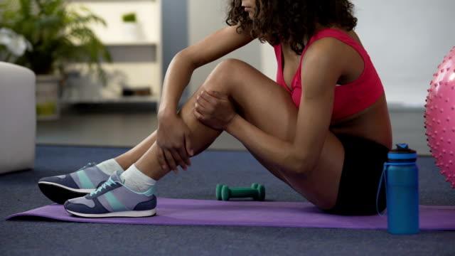 vidéos et rushes de fille en tenue de gym assis sur le plancher et le massage de jambe étroit, tendues de muscle - veau