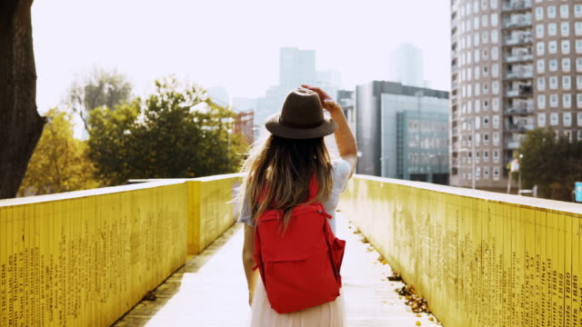 girl in hat with long hair walks on a city bridge. caucasian woman between yellow walls with red backpack. back view 4k - cappello video stock e b–roll